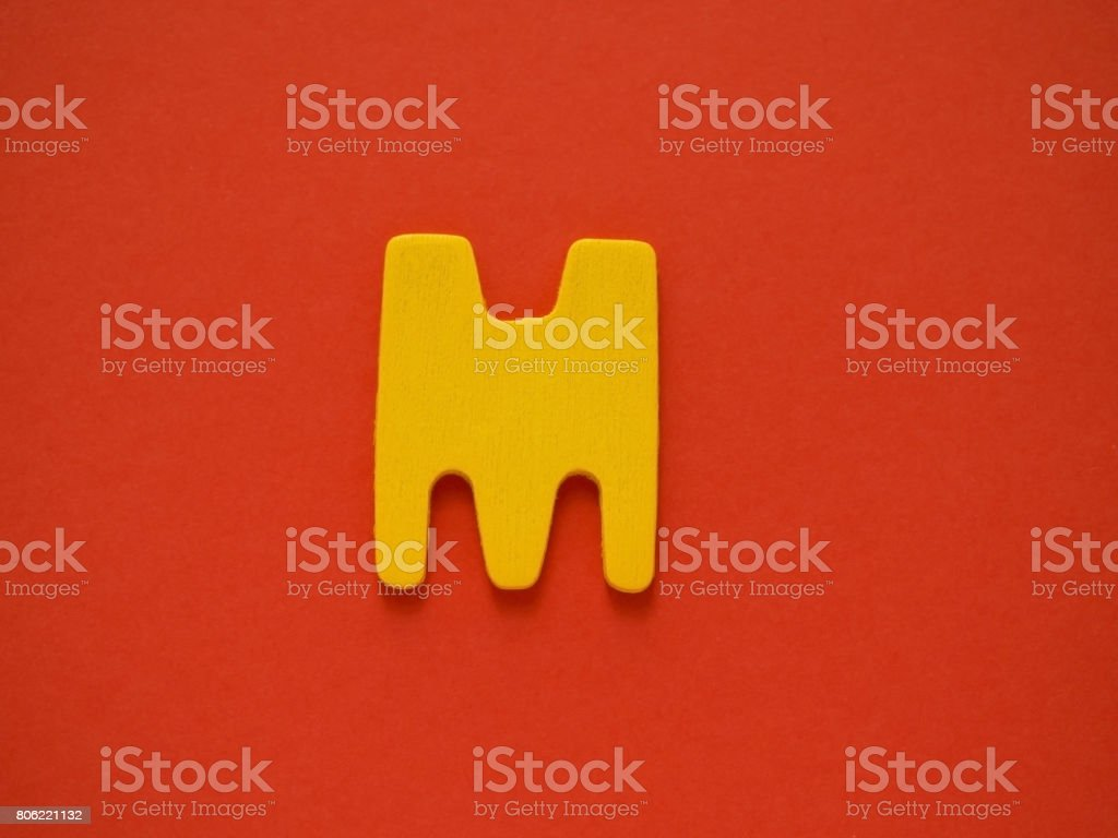Capital letter M. Yellow letter M from wood on red background. stock photo