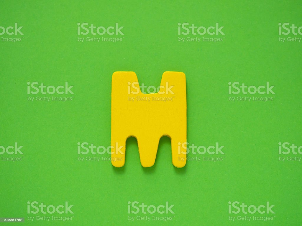 Capital letter M. Yellow letter M wood on green background. stock photo