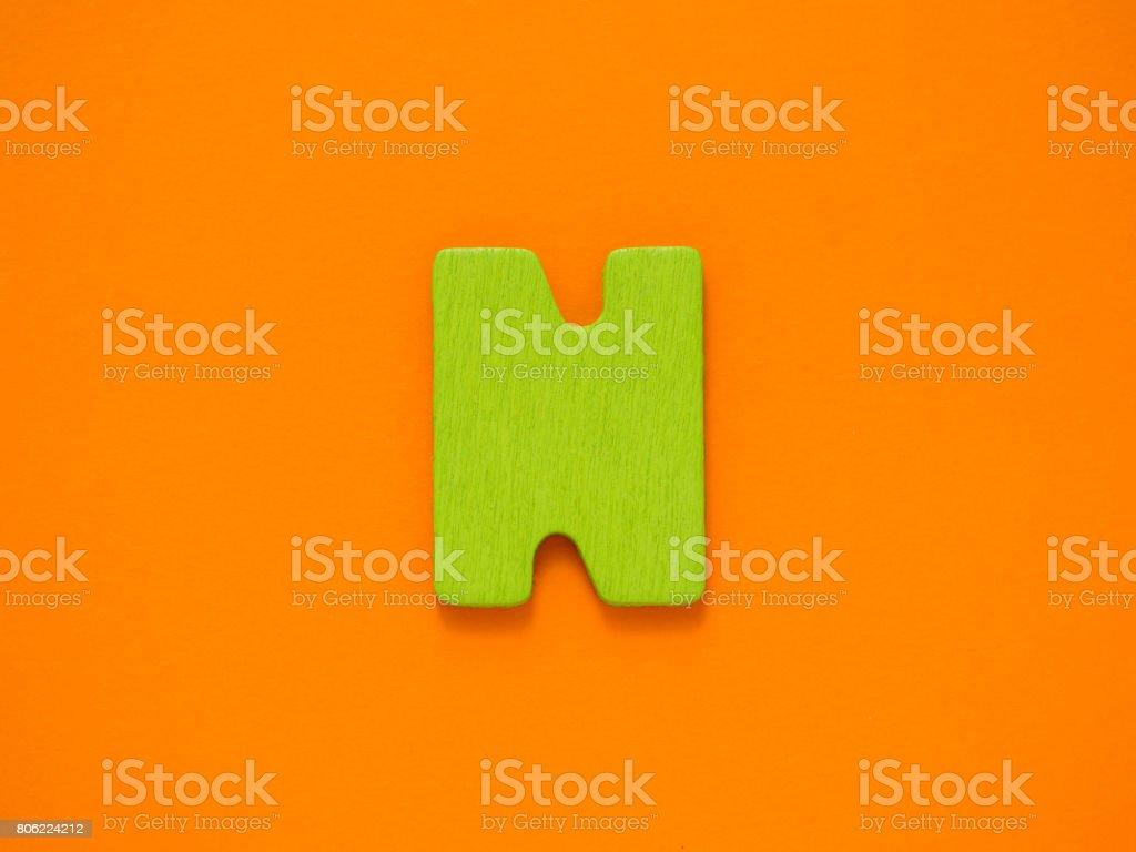 Capital letter N. Green letter N from wood on orange background. stock photo