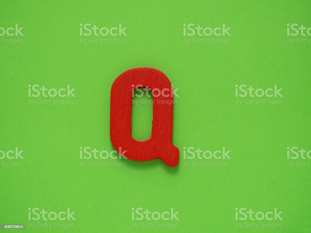 Capital letter Q. Red letter Q from wood on green background. stock photo