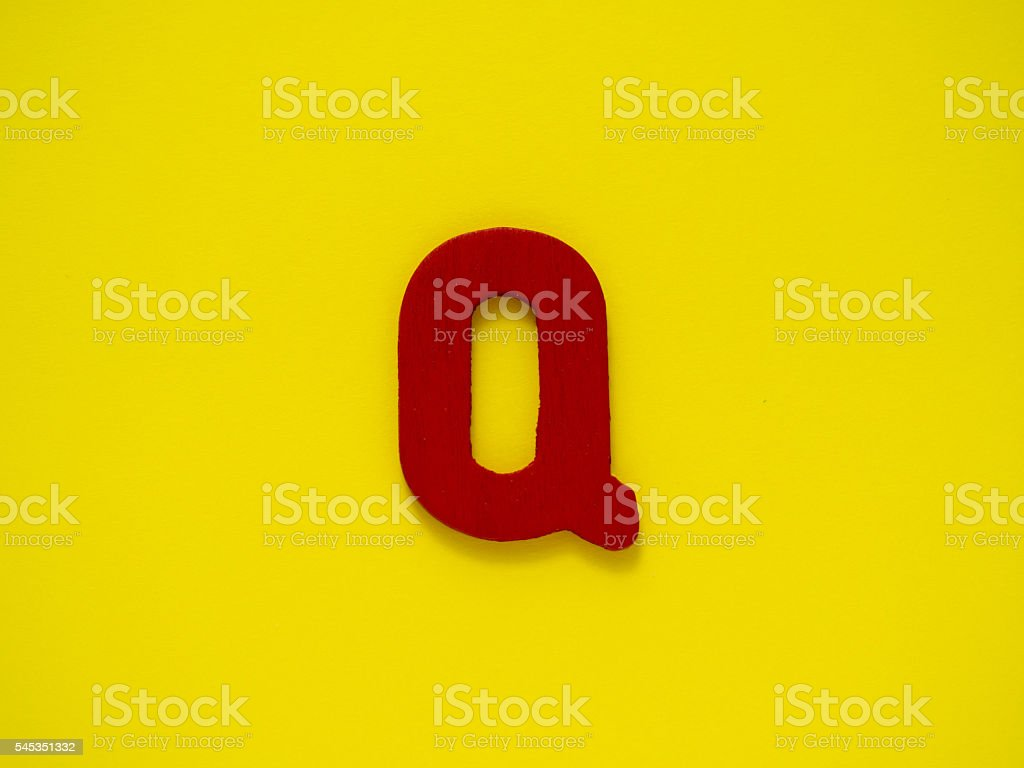 Capital letter Q. Red letter Q wood on yellow background. stock photo