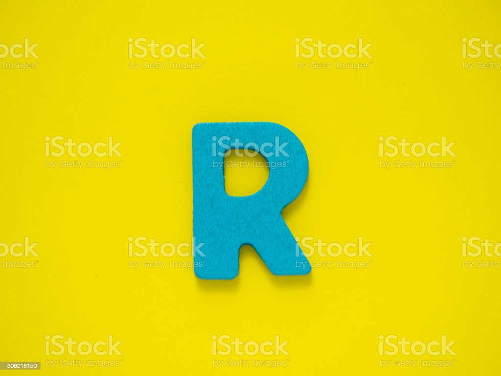 Capital letter R. Blue letter R from wood on Yellow background. stock photo