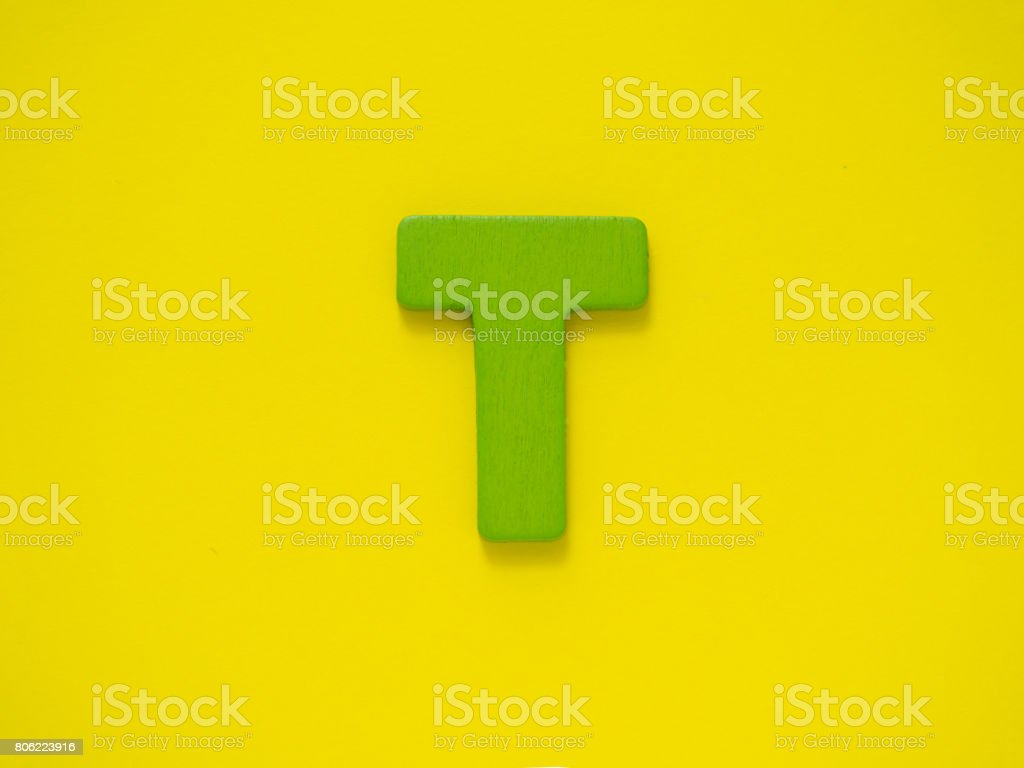 Capital letter T. Green letter T from wood on yellow background. stock photo