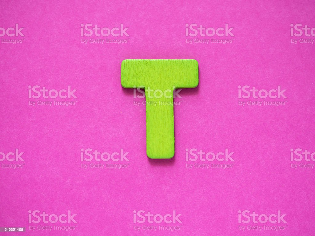 Capital letter T. Green letter T wood on purple background. stock photo