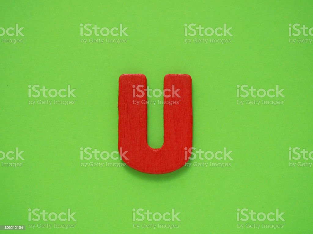 Capital letter U. Red letter U from wood on green background. Alphabet vowel. stock photo