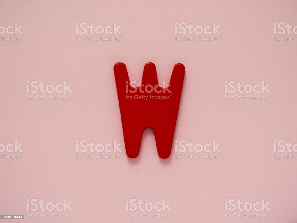 Capital letter W. Red letter W from wood on pink background. stock photo