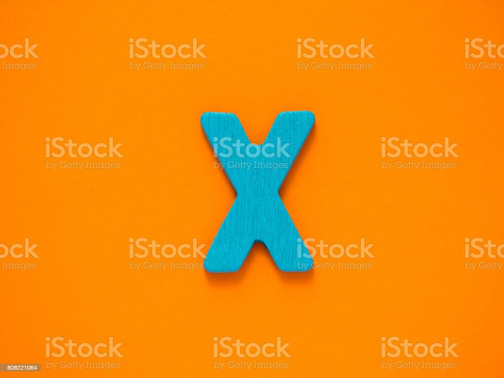 Capital letter X. Blue letter X from wood on orange background. stock photo