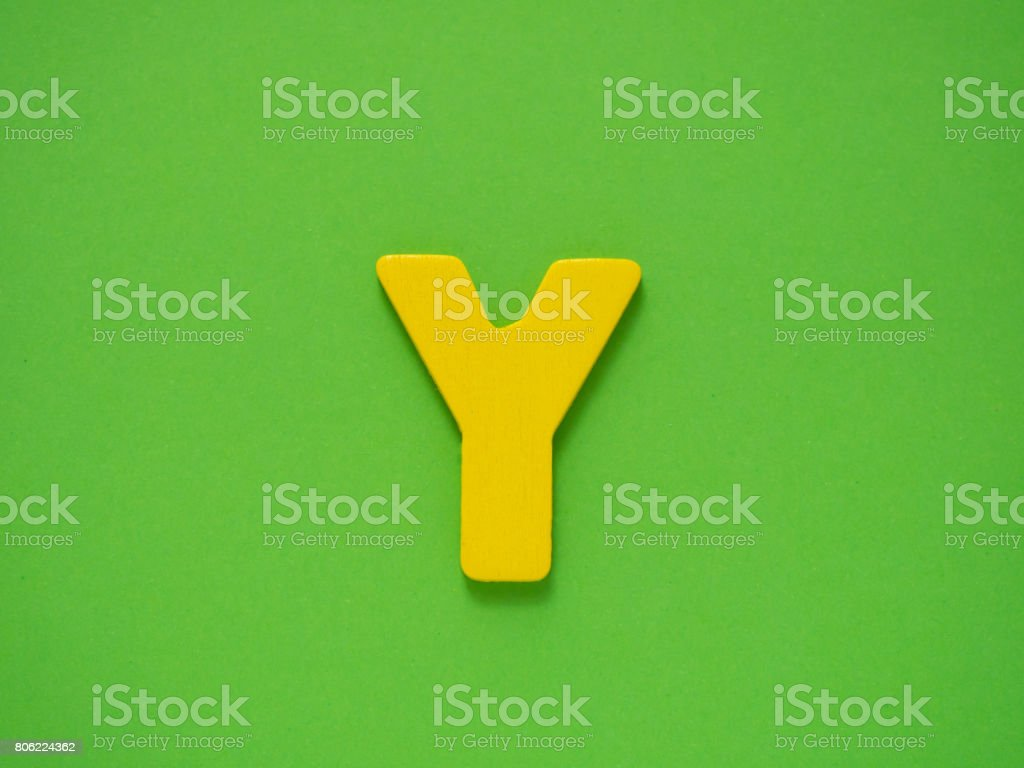 Capital letter Y. Yellow letter Y from wood on green background. stock photo