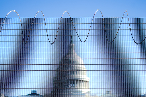 Fences were erected around Capitol after January 6 2021 when pro-Trump protesters rallied in DC ahead of Electoral College vote count and some stormed into the Capitol. Fully armed National Guard soldiers on guard.