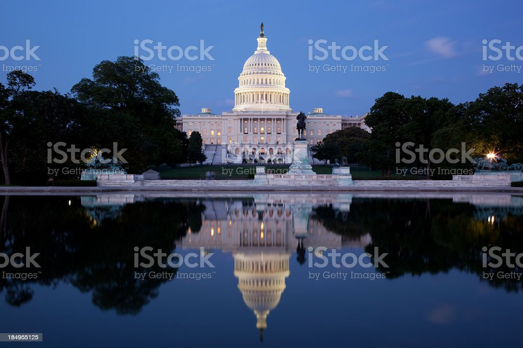 U S Capitol building lit up at dusk reflecting into pool stock photo