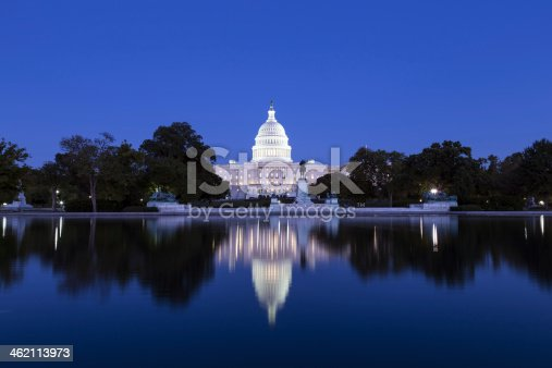 US Capitol in the dusk illuminated with lights reflecting in the pool