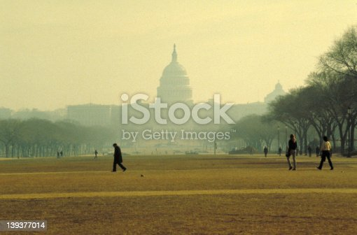 US Capitol from the Mall, shot early in the morning haze, a few people walking by.