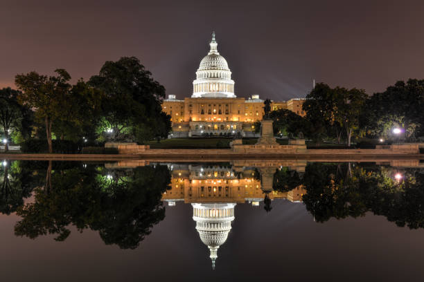 US Capitol in Washington DC at night The US Capitol Building as seen across the reflecting pool at night in Washington, DC. capitol hill stock pictures, royalty-free photos & images