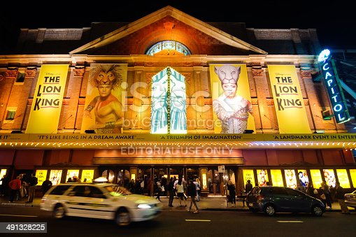Sydney, Australia - May 15, 2014: A taxi leaves after dropping off a passenger at historic Capitol Theatre on Campbell St at night. Other patrons are gathered around the entrance, awaiting a performance of Disney's The Lion King.