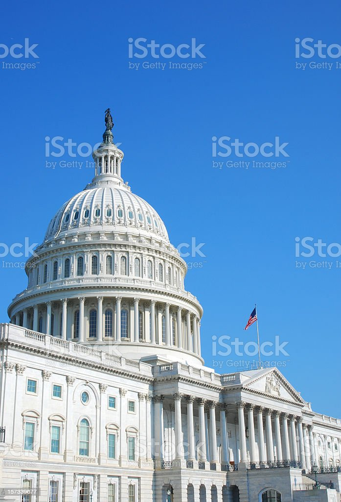 U.S. Capitol with clear sky and flag flying royalty-free stock photo