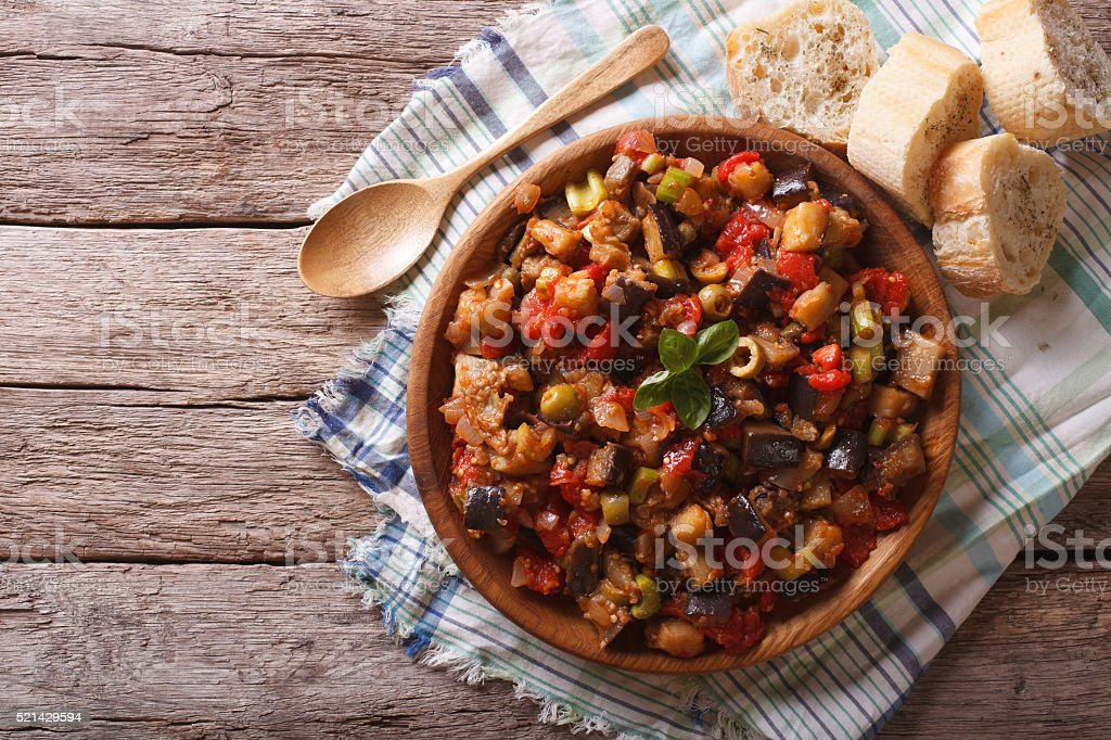 Caponata with aubergines in a wooden plate. Horizontal top view stock photo