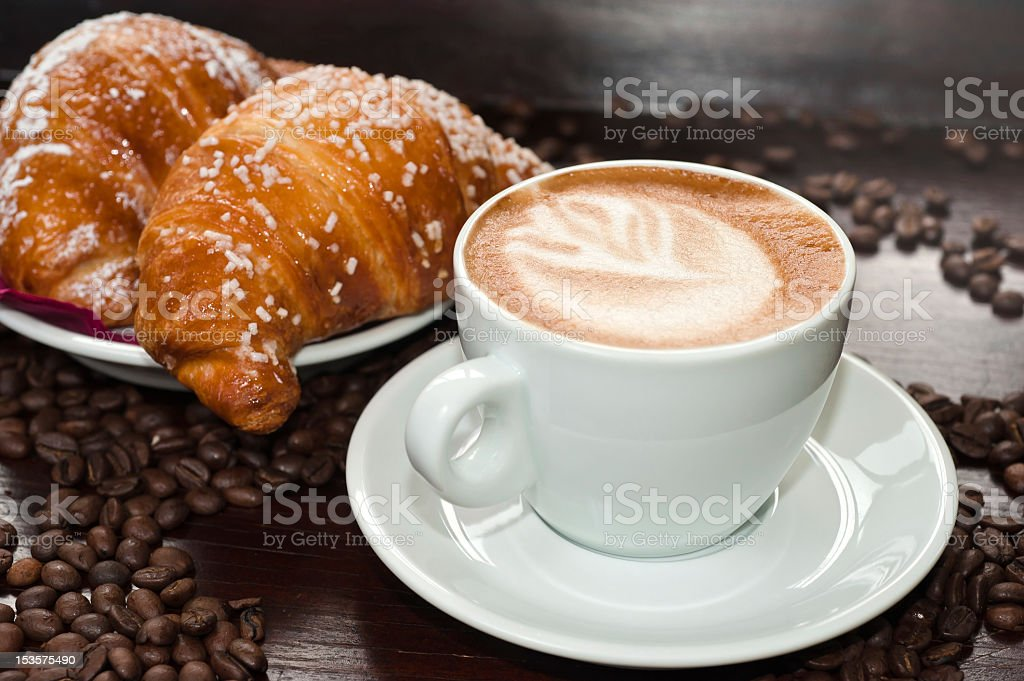 Cappuccino and croissants on a table with coffee beans royalty-free stock photo