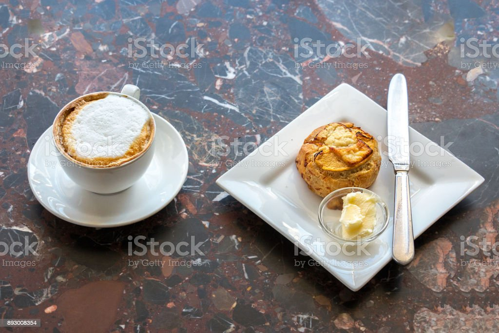 A cappuccino and one scone on a counter. stock photo