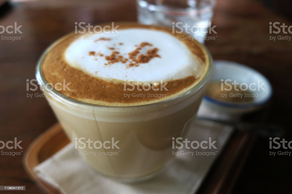 cappuccino and sugar, water on wood table top, bangkok, thailand