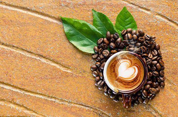 Cappuccino coffee in a mug with coffee beans & leaves stock photo