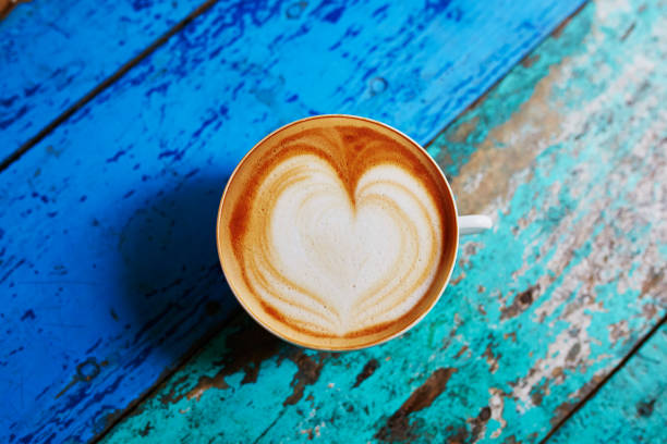 cappuccino coffee on colorful green and blue cafe table - kaffeetasse bild stock-fotos und bilder
