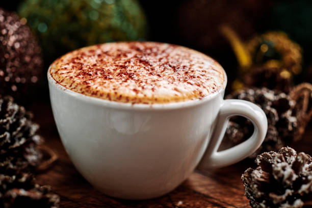 Cappuccino Coffee surrounded by pine cones and Christmas decorations on a dark rustic wood tabletop. stock photo