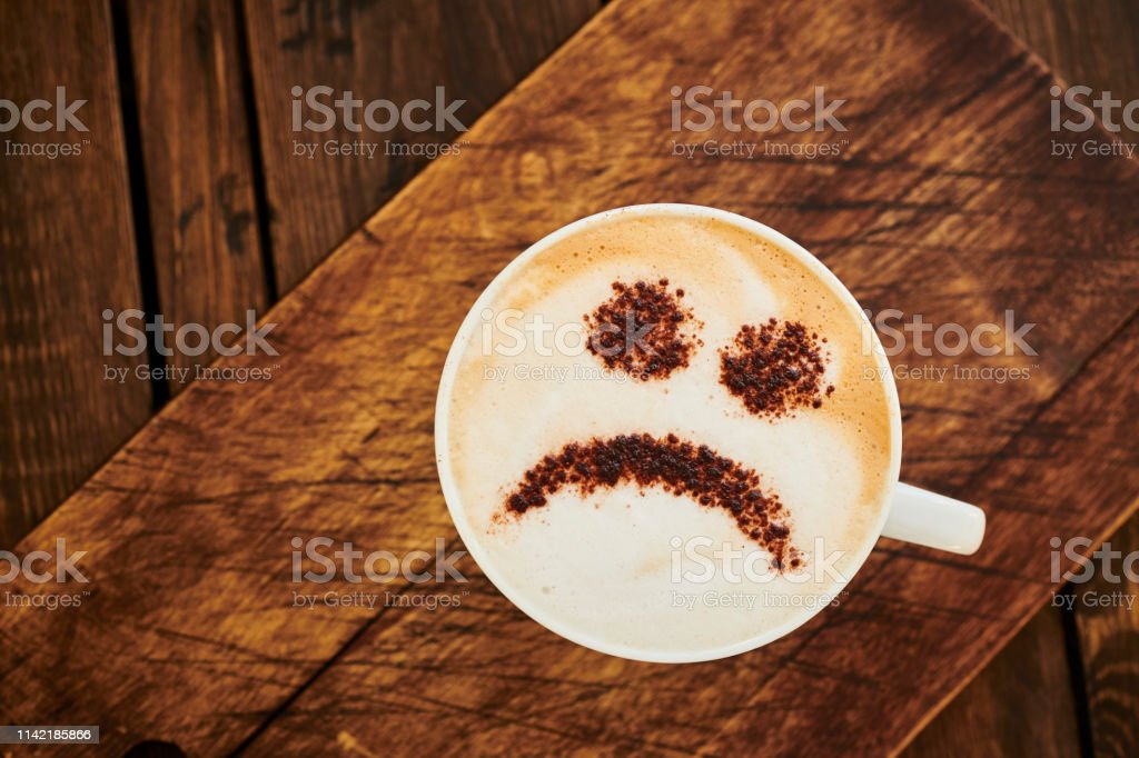Cappuccino Coffee topped with a chocolate unhappy smiley face. stock photo