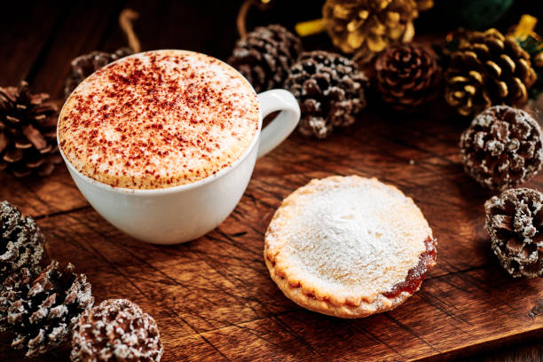 Cappuccino Coffee with a Mince Pie surrounded by pine cones and Christmas decorations on a dark rustic wood tabletop.