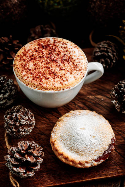 Cappuccino Coffee with a Mince Pie surrounded by pine cones and Christmas decorations on a dark rustic wood tabletop. stock photo
