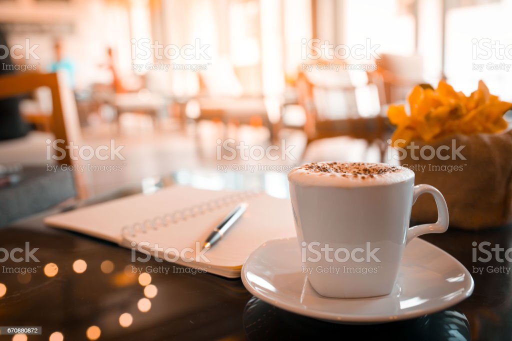 Cappuccino coffee,notebook and pen on table in the morning stock photo