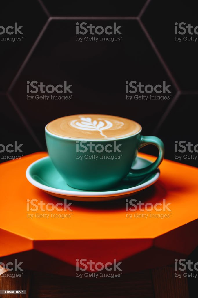 Cappuccino. Cup of Cappuccino Coffee on orange table