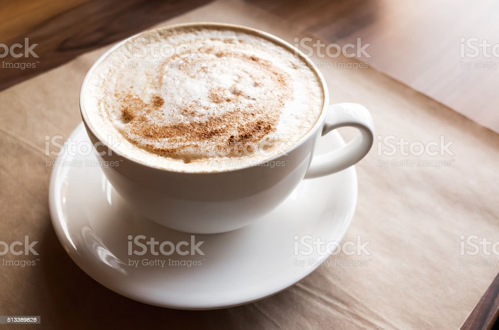 Cappuccino. Cup of coffee stands on old paper stock photo