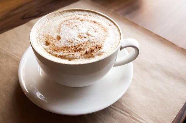 cappuccino. eine tasse kaffee steht auf alten papier - mocca stock-fotos und bilder