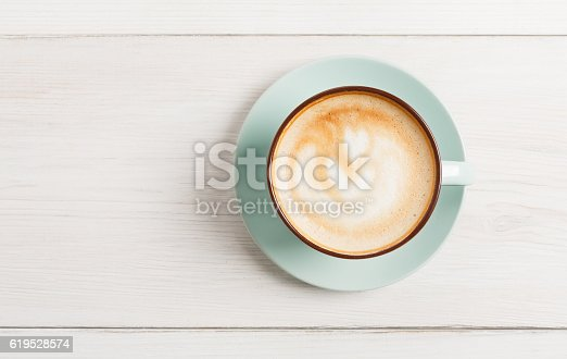 istock Cappuccino foam, coffee cup top view on white wood background 619528574