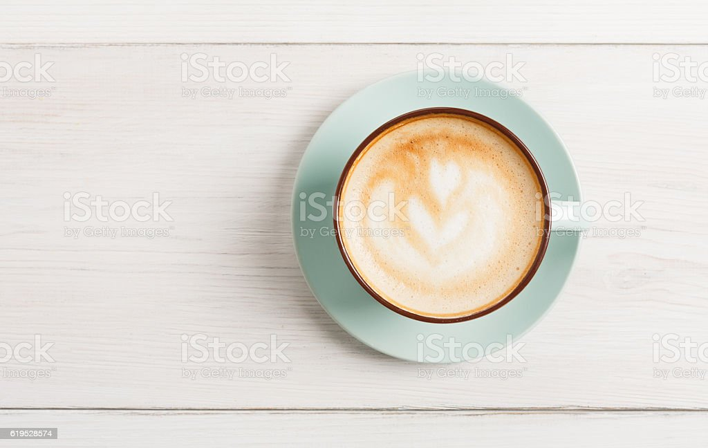 Cappuccino foam, coffee cup top view on white wood background stock photo