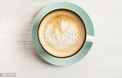 istock Cappuccino foam, coffee cup top view on white wood background 838102504
