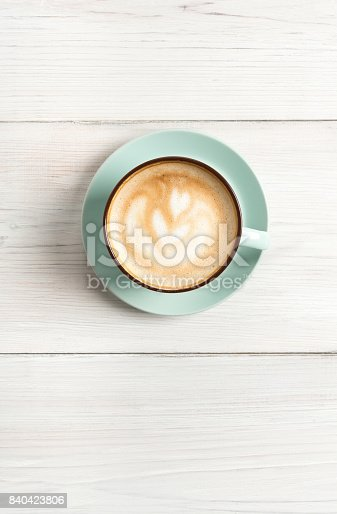 istock Cappuccino foam, coffee cup top view on white wood background 840423806