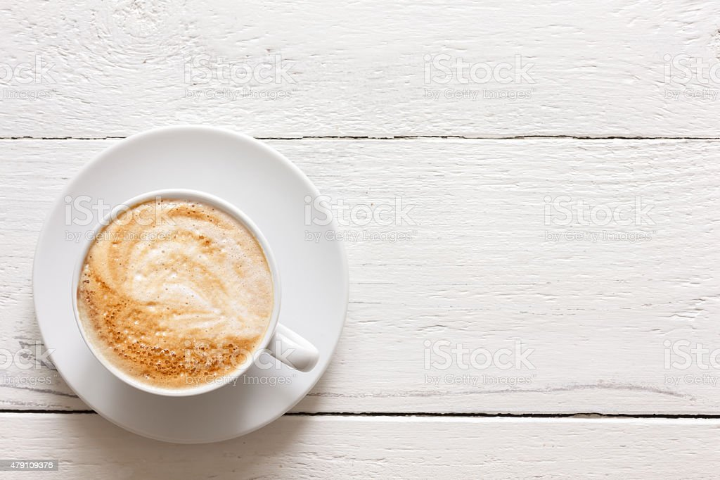 Cappuccino in cup on rustic painted wood. stock photo