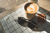 cappuccino in take away coffee cup on table cloth with dry flower,sunglasses on wood table with sunlight hard shadow at window in evening.food and drink lifestyle leisure concept