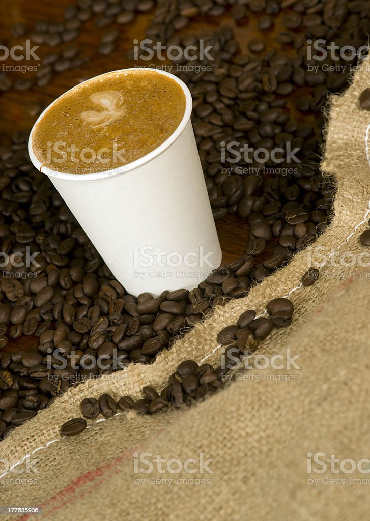 Cappuccino IN To Go Cup With Spilled Coffee Beans Burlap royalty-free stock photo