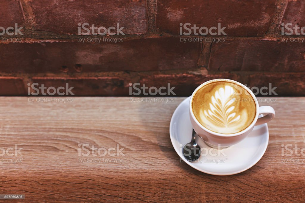 Cappuccino on the table near brick wall royalty-free stock photo
