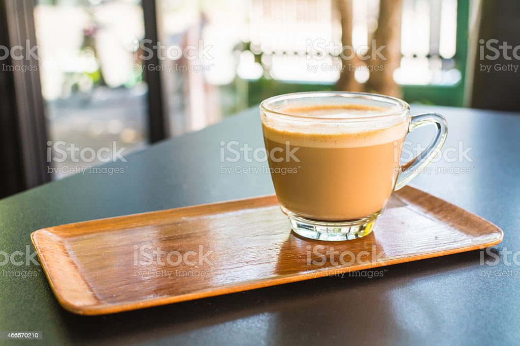 Cappuccino or latte coffee in a clear glass mug. stock photo