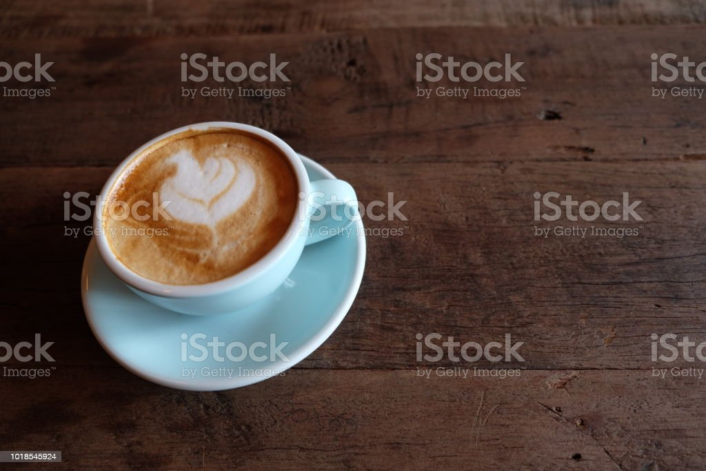 Cappuccino or latte with frothy foam, blue coffee cup top on wooden...