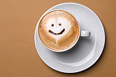 Cup of cappuccino with smiley face.