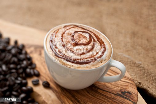 Cappuccino topped with swirls of chocolate sauce.