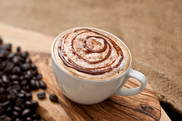 cappuccino topped with swirls of chocolate sauce - chocolate syrup stock photos and pictures