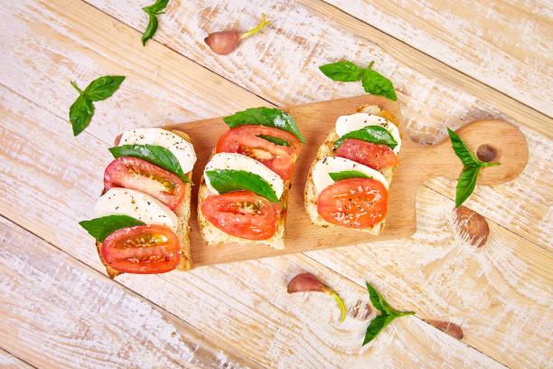 Caprese bruschetta toasts auf dem Schneidebrett. Bruschetta mit Tomaten, Mozzarella-Käse und Basilikum auf einem rustikalen Tisch. Traditionelle italienische Vorspeise oder Snack, Antipasto – Foto