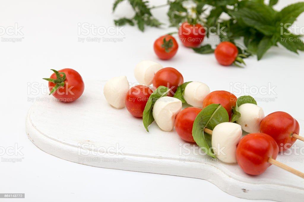 Caprese of mozzarella, tomato cherry and basil, tradition mediterranean snack, on white royalty-free stock photo