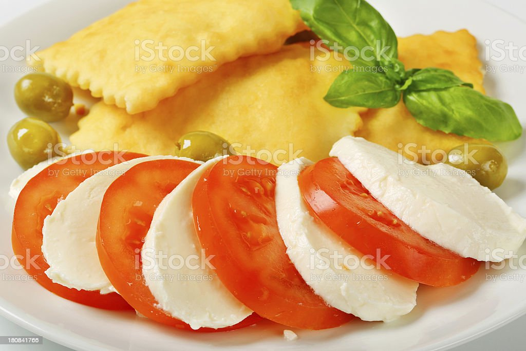 Caprese salad and fried dough puffs royalty-free stock photo