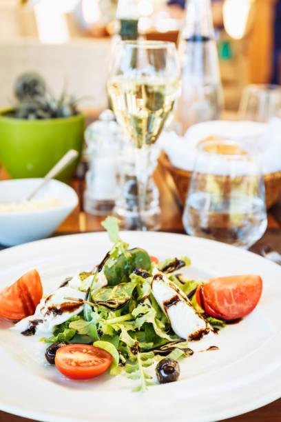 caprese-salat am tisch. outdoor-italienisches restaurant-terrasse. konzept der sommer authentische mahlzeit - carpaccio salat stock-fotos und bilder